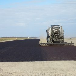 In this picture West-Can is fog coating a washed chip seal project on a private runway to help retain the aggregate in place