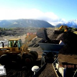 Using an excavator to break up large piles of asphalt millings to be processed through the pug mill and paved shortly after