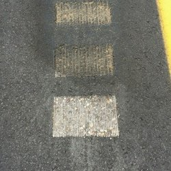 Sand Sealing rumble strips on paving project, notice the difference between the treated and untreated asphalt milled surface.